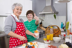 Happy family: Grandmother and grandson cooking together. royalty free stock photo