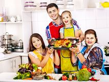 Happy family with grandmother at kitchen. Cooking chicken Royalty Free Stock Photos
