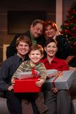 Happy family with grandparents at christmas. Portrait of happy family together with grandparents at christmas eve, holding presents, smiling Stock Photo