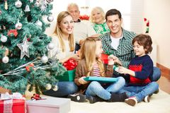 Family making gift giving at christmas eve. Happy family with grandparents making gift giving at christmas eve stock images