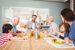 Happy family with grandparents sitting at dining table Stock Photo