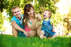 Happy family on a green lawn in park Stock Photo