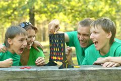 Happy family in green shirts playing Royalty Free Stock Photos