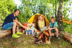 Happy family grilling marshmallows on a sticks Stock Photography