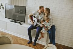 Happy family with guitar. At home stock photos