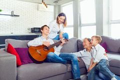 Happy family with guitar singing songs in the room. Happy family with guitar singing songs sitting in the room Royalty Free Stock Photo