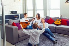 Happy family with guitar singing songs in the room. Happy family with guitar singing songs sitting in the room stock photo