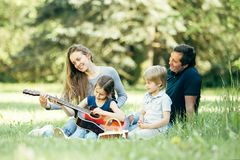 Happy family with a guitar, sitting on the lawn in the Park. Concept of family leisure. happy family with a guitar, sitting on the lawn in the Park stock photo
