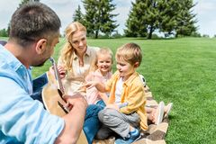 Happy family with guitar sitting together on plaid. At picnic stock photos