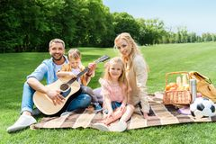 Happy family with guitar smiling at camera while sitting together on plaid. At picnic royalty free stock photo