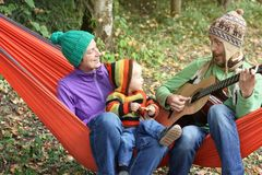 Happy family in hammock in autumn forest. Father playing on guitar, mother and son listening.  stock photo