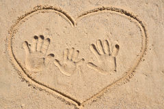 Drawing heart with family hand print. Drawing heart with family hand print on sand.Concept of family traveling, vacation, happiness family Stock Photography