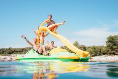 Happy family hands up on floating Playground slide Catamaran as they enjoying sea trip durins summer vacation stock photos