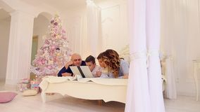 Happy family happily spends time together and uses computer, lying on bed in bright bedroom with Christmas tree and stock video footage
