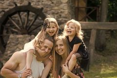 Happy family. Happy childhood, family, love. Children and parents visit old stone mill. Mothers, fathers day. Girls sit on women and men shoulders. Summer Royalty Free Stock Photography