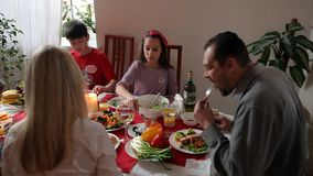 Happy family has holiday dinner. With a fish and a vegetables stock footage