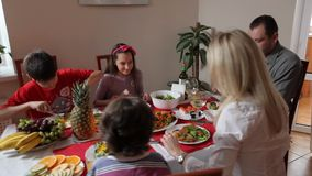 Happy family has holiday dinner. With a fish and a vegetables stock video footage