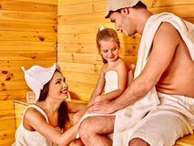 Happy family  in hat  at sauna. Happy family with child in hat  relaxing at sauna Stock Photography