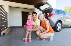 Happy family with hatchback car at home parking. Transport, leisure, road trip and people concept - happy family with little girl and hatchback car at home stock photography