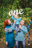 Happy family have birthday party in a forest and hold One sign stock photography