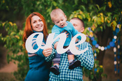 Happy family have birthday party in a forest and hold One sign Stock Photo