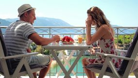 Happy family have a breakfast sitting on a balcony. At beautiful island background stock footage