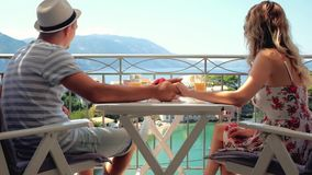 Happy family have a breakfast sitting on balcony at beautiful island background. Happy family have a breakfast sitting on a balcony at beautiful island stock footage