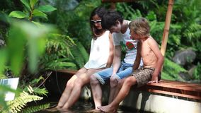 Happy family have a fish spa in natural pond in tropical jungle. 1920x1080. Hd stock footage