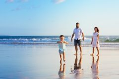 Happy family have fun on sunset beach. Happy family - father, mother, baby son have fun together, child run with splashes by water pool along sunset sea surf on Royalty Free Stock Photography