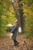 Happy family have fun walking in autumn park - The mother playing with her daughter among the yellow leaves Royalty Free Stock Image