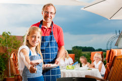 Happy family having a barbecue Stock Image