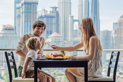 Happy family having breakfast on the balcony. Breakfast table with coffee fruit and bread croisant on a balcony against. The backdrop of the big city stock images
