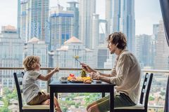 Happy family having breakfast on the balcony. Breakfast table with coffee fruit and bread croisant on a balcony against. The backdrop of the big city stock photos