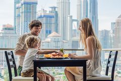 Happy family having breakfast on the balcony. Breakfast table with coffee fruit and bread croisant on a balcony against stock photo