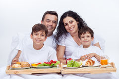 Happy family having breakfast in bed Stock Image