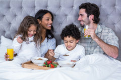 Happy family having breakfast on bed Stock Photo