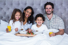 Happy family having breakfast on bed Royalty Free Stock Images