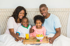 Happy family having breakfast in bed together Stock Photo
