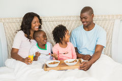 Happy family having breakfast in bed together Royalty Free Stock Photography