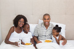 Happy family having breakfast in bed together in the morning Stock Images
