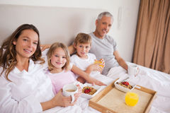 Happy family having breakfast in a bedroom Royalty Free Stock Photo