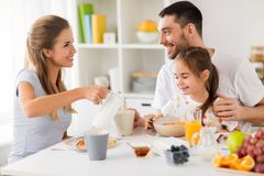 Happy family having breakfast at home stock photo