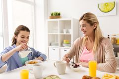 Happy family having breakfast at home kitchen. Food, healthy eating, family and people concept - happy mother and daughter having breakfast at home kitchen Royalty Free Stock Photos