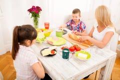 Happy family having breakfast at home Stock Photography