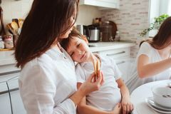 Happy family having breakfast at home. Mother with two kids eating in the morning in modern white kitchen Stock Photos