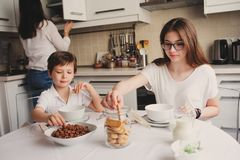 Happy family having breakfast at home. Mother with two kids eating in the morning in modern white kitchen Stock Photo