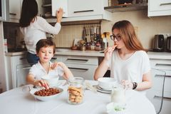 Happy family having breakfast at home. Mother with two kids eating in the morning in modern white kitchen Stock Photography