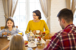 Happy family having breakfast in the kitchen of their house Stock Images
