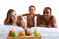 Happy family having breakfast and looking at the camera in bed. Royalty Free Stock Image