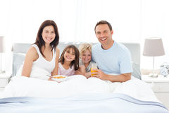Happy family having breakfast together on the bed Stock Image